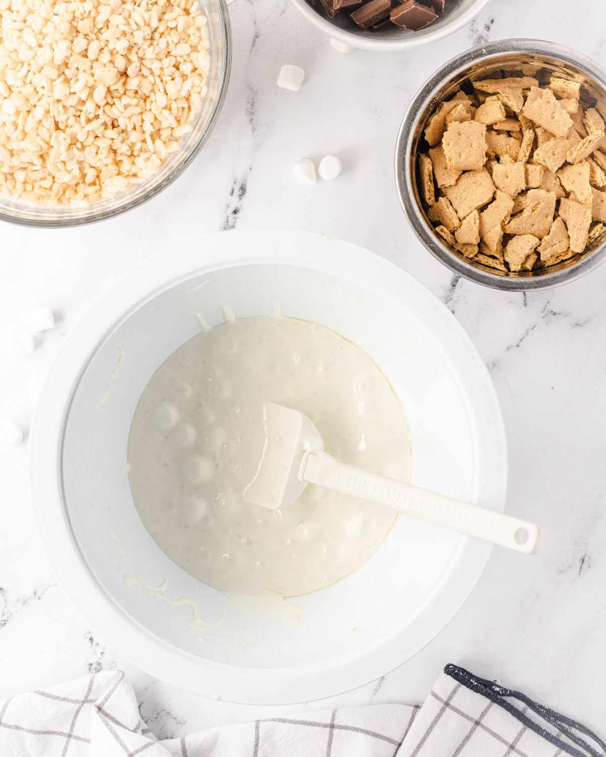 Melted marshmallows in a large bowl, with a bowl of rice krispies and a bowl of graham cracker pieces above it.