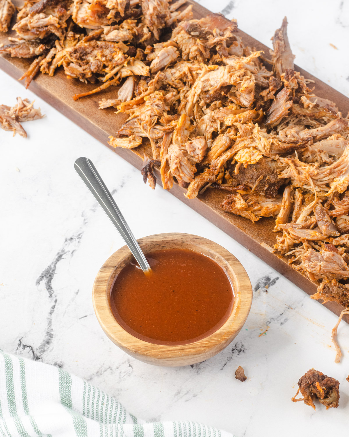 wooden bowl with bbq sauce in front of a wooden platter of shredded pork.