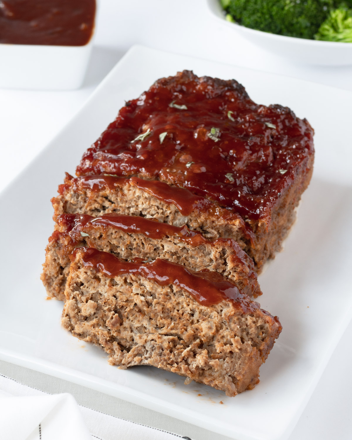 Meatloaf topped with sauce on a white plate.