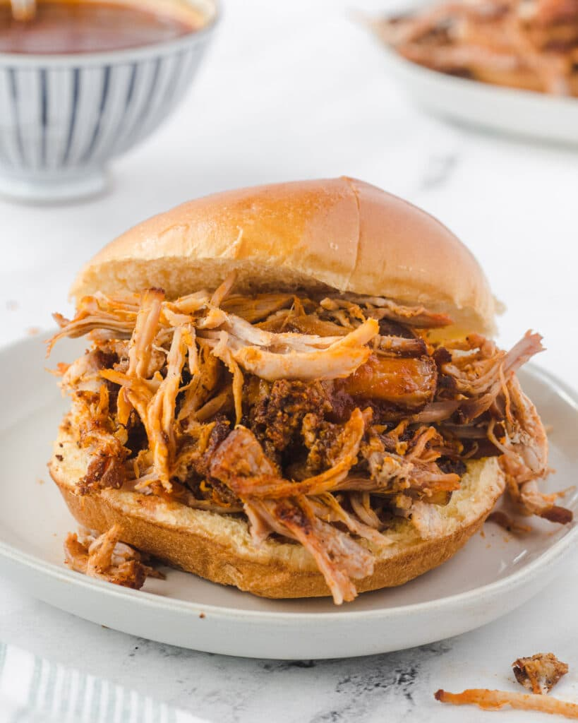 Pulled pork sandwich on a plate, with bowl of bbq sauce behind it.
