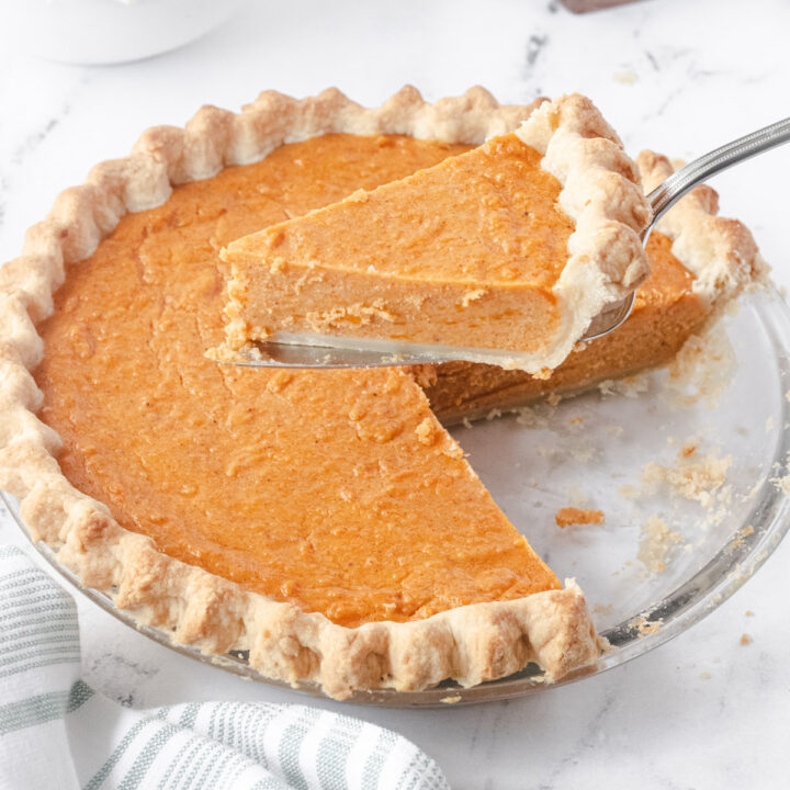 A slice of pie being removed from the pie plate.