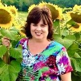 Photo of a woman standing in sunflowers.