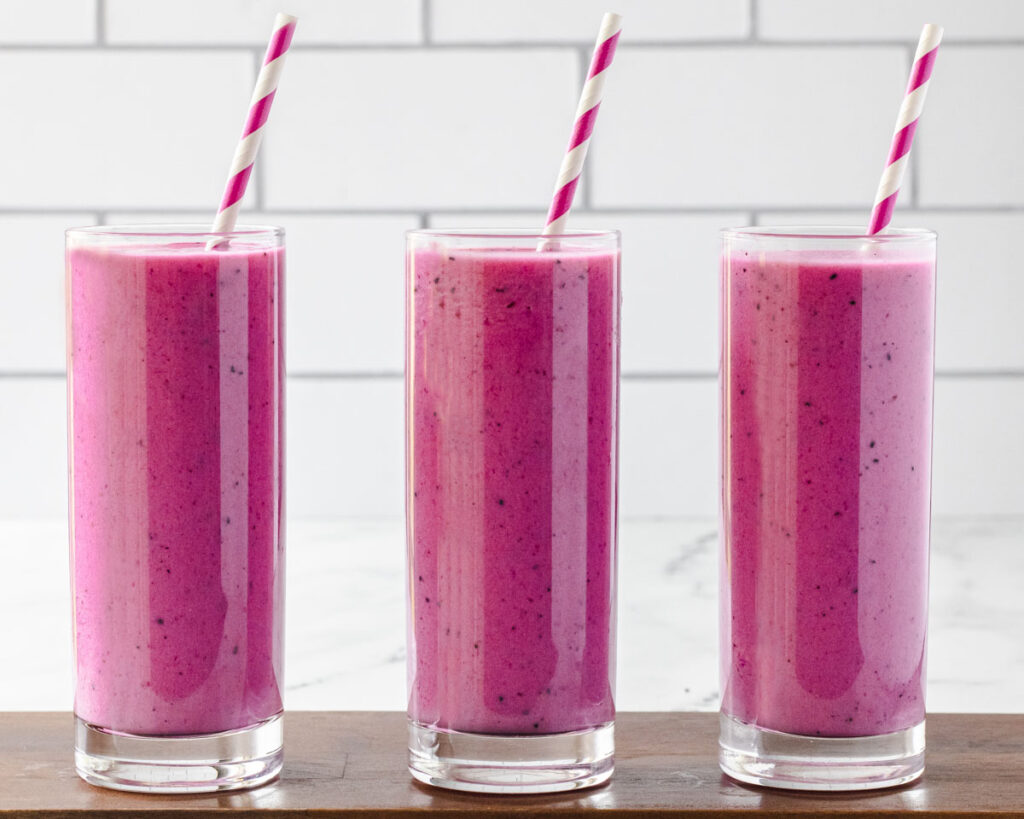 3 glasses of dragon fruit smoothie side by side on a wooden board.