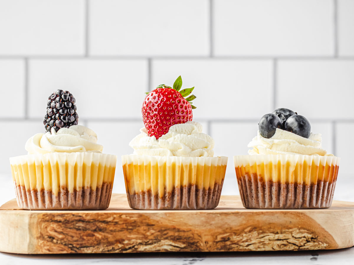 3 cheesecakes on a row, 1 topped with blackberry, 1 with strawberry, and 1 with 3 blueberries.