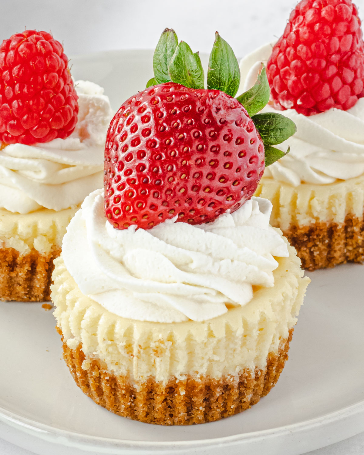 Close up of 3 mini cheesecakes on a plate, with whipped cream and strawberry on front one, and raspberry on back 2.