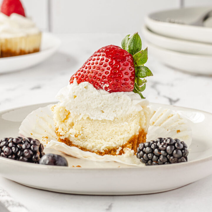 Cheesecake on a plate with a bite out of it.
