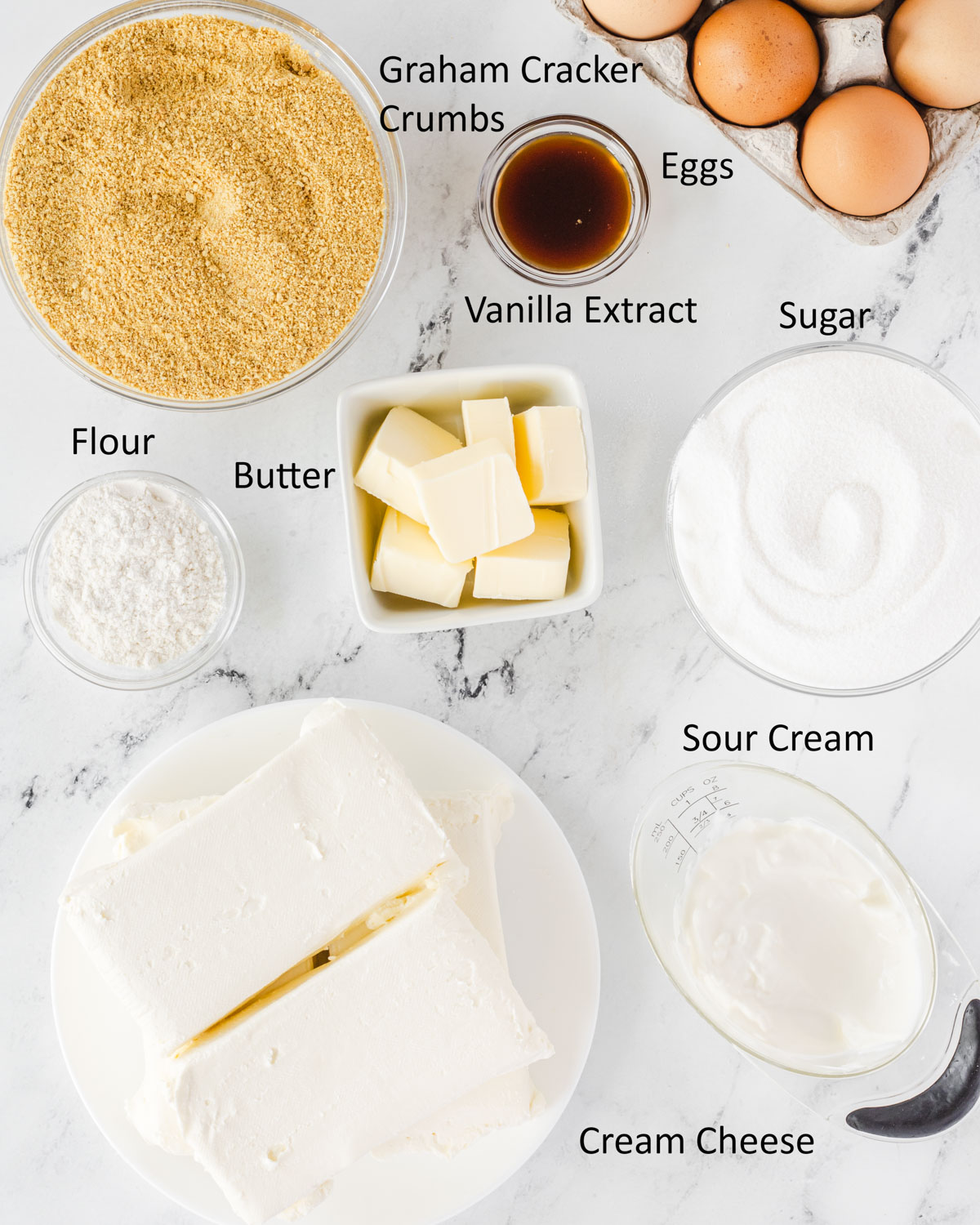 Overhead shot of labeled cheesecake ingredients.