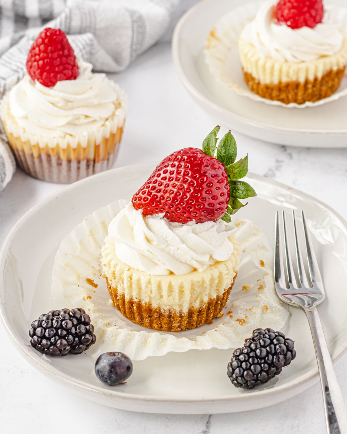 Mini new york cheesecake on a plate with berries and a fork, and two more cheesecakes in background.