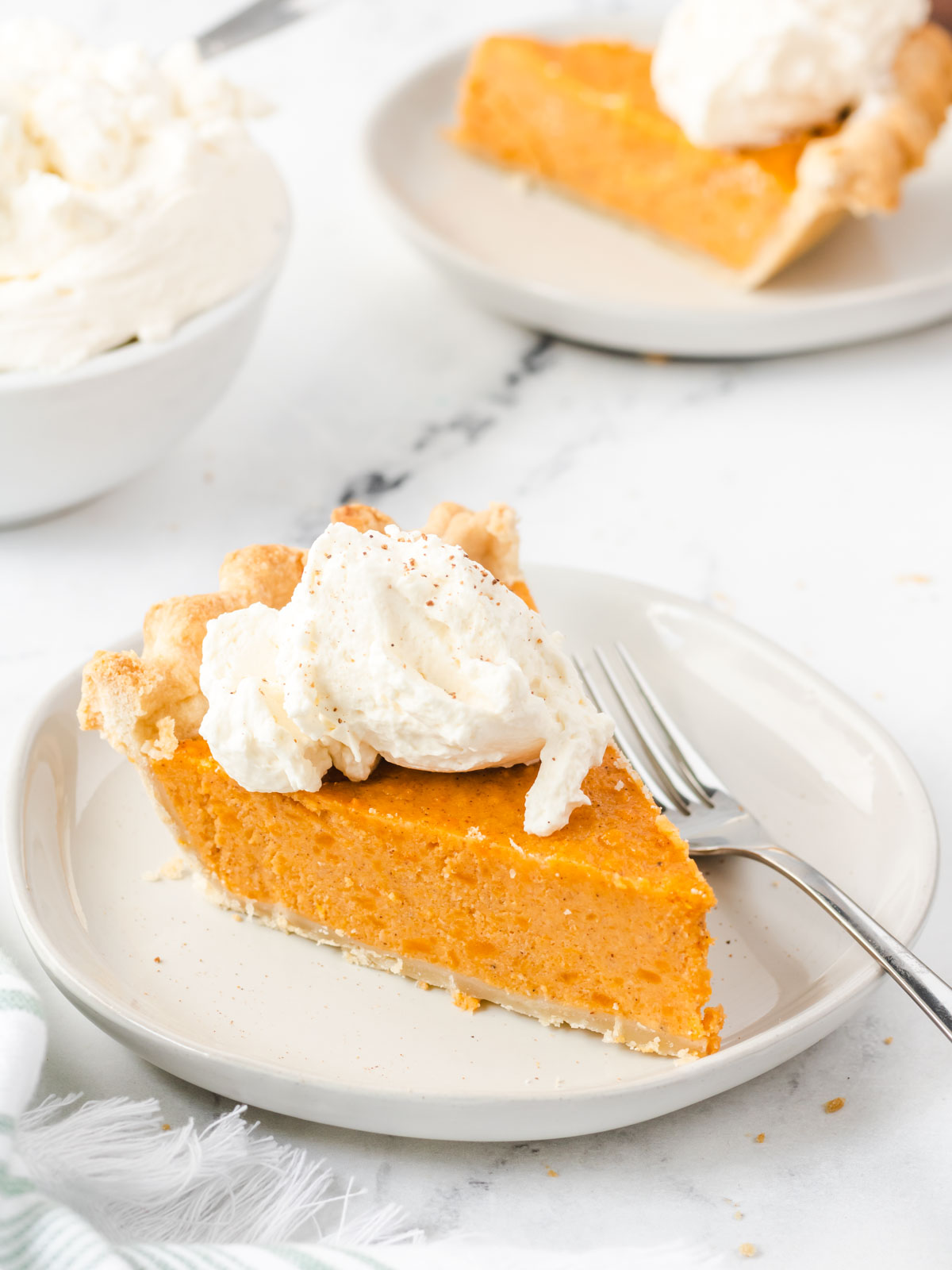 Two plates of sweet potato pie with dollaps of whipped cream.
