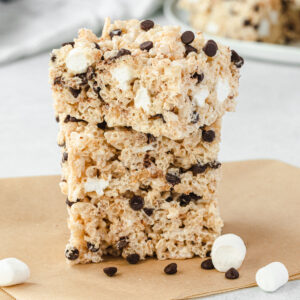 Stack of 3 chocolate chip rice krispie treats with some mini marshmallows and chips sprinkled on parchment.