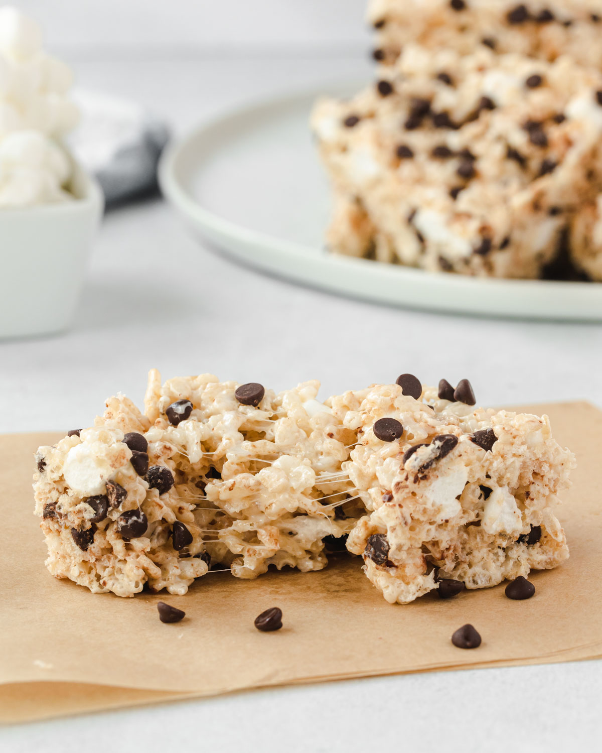 Chocolate chip rice krispie treat on a bown parchment square, pulled apart to show gooey marshmallow.