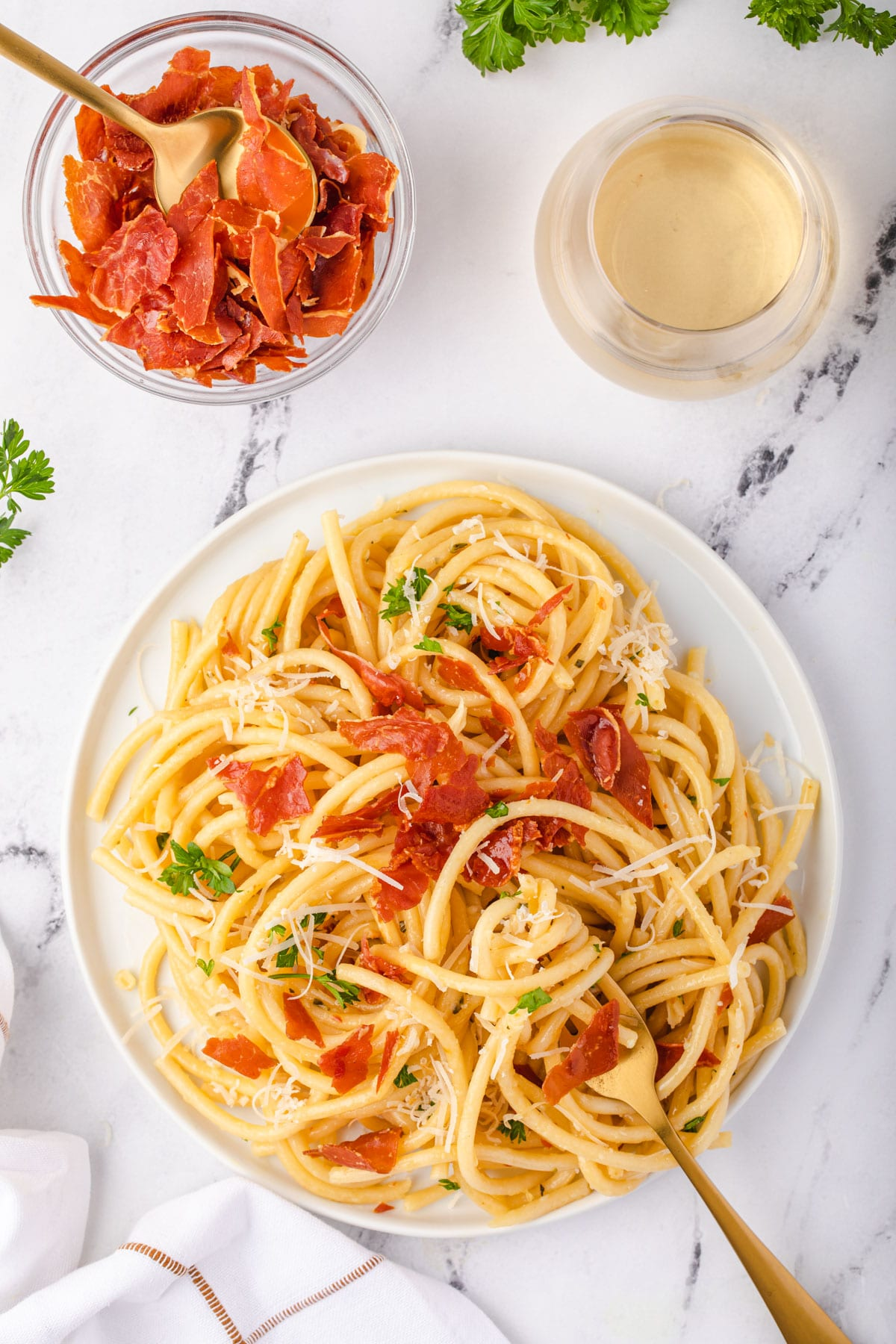 Plate of pasta in front of a bowl of crispy prosciutto and a glass of wine.