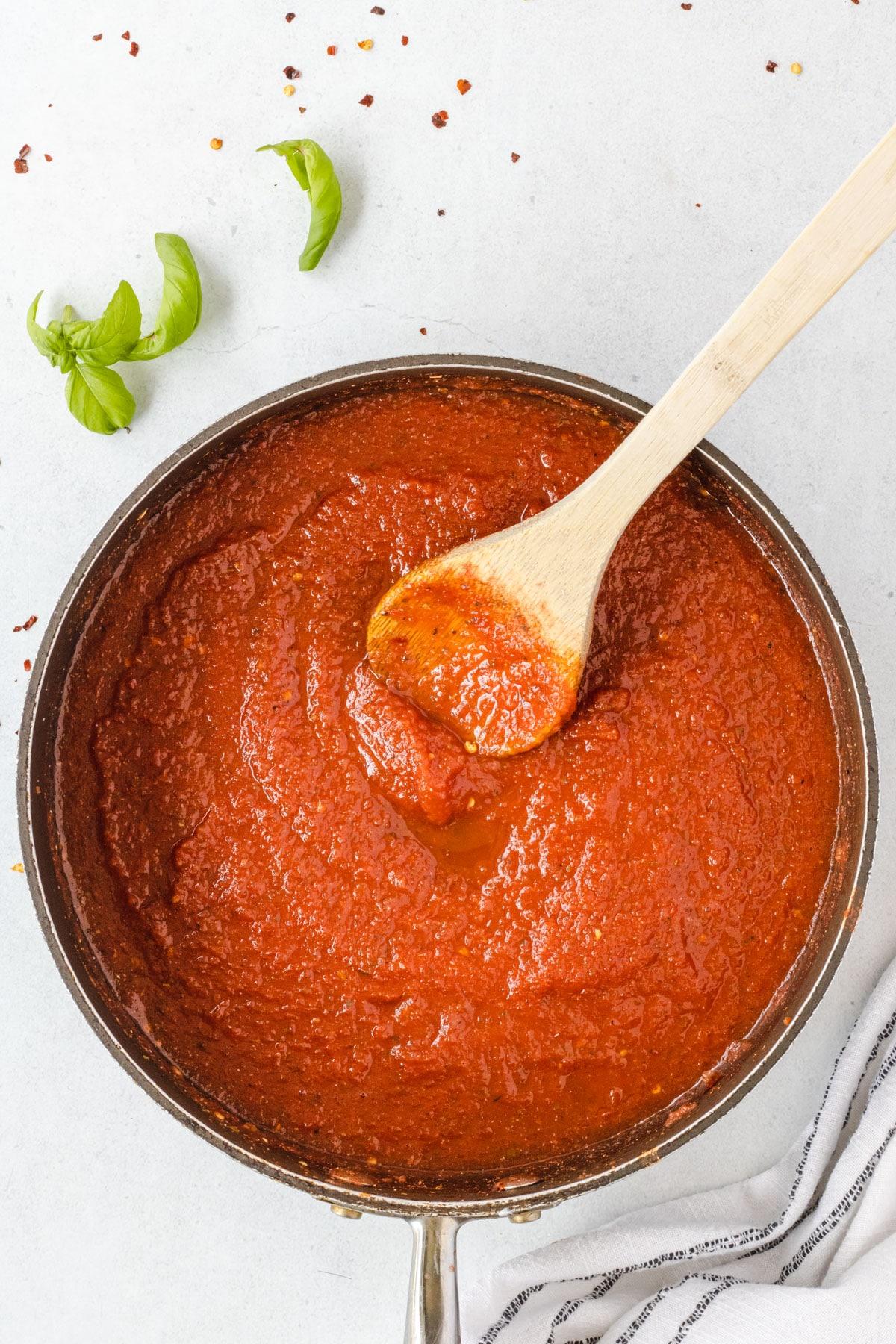 Wooden spoon stirring sauce.