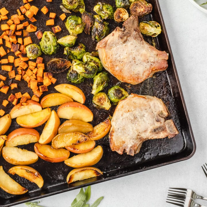 Sheet pan angled with roasted dinner on it, and sage leaves framing the pan.