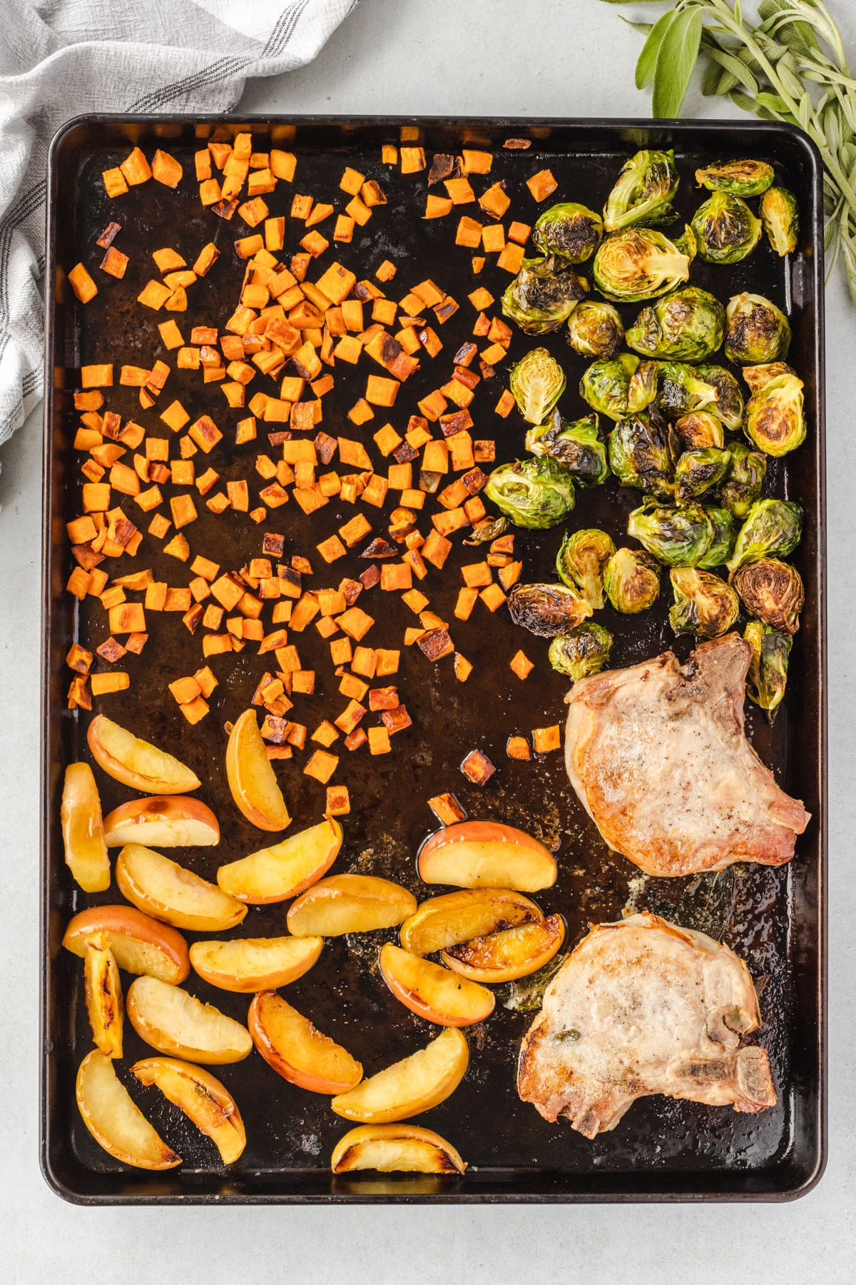Overhead shot of sheer pan with roated vegetables, apples, and pork.