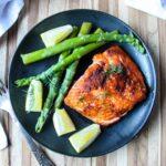 Salmon on black plate with asparagus.