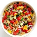 Bowl of pasta salad with tomatoes, cucumber, olivers, and peppers.